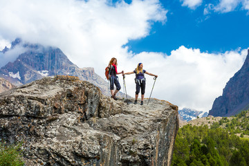Outdoor life. People walking on top of stone rock with trekking poles and backpacks silhouettes on clouds and sky background mountain landscape young women