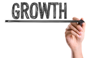 Hand with marker writing the word Growth