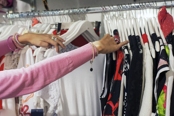 Young pretty woman buying, looking at fashion female clothes