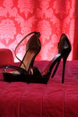 Hochhackige Schuhe auf rotem Bett
