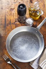 an empty pan on a wooden table. salt, pepper, olive oil. space f