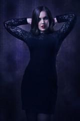 Pretty woman in a black dress in the dark room