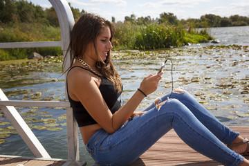 Adolescente de 15 años escuchando música en el embarcadero. Chica rubia adolescente escuchando música con los cascos de su teléfono.