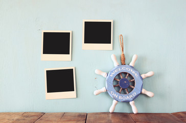 blank instant photos hang over wooden textured background next to vintage wheel