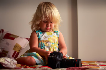 little blonde girl examines camera against white wall