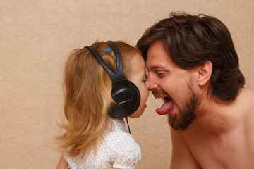 Little girl and dad listens to music.
