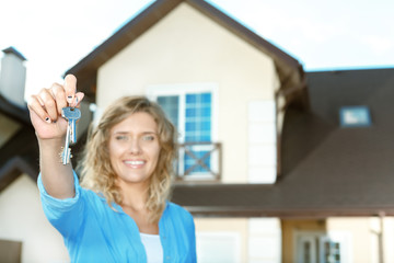 Happy girl with keys next to her new house
