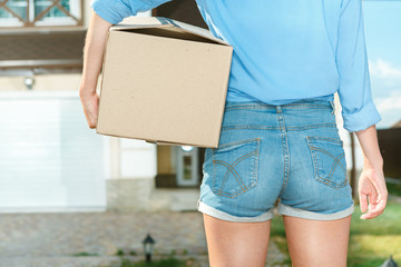 Young woman carrying boxes in to new house