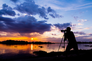 silhouette of photographer taking photo at sunset beside the riv