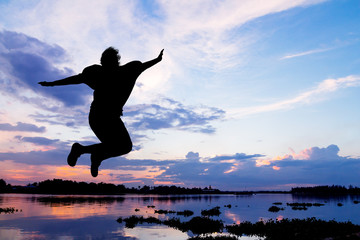 Lady jumping happy beside the river at sunset