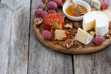 soft cheeses and snacks and wooden background