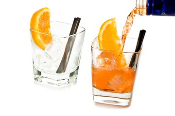 Fototapete - barman pouring spritz aperitif aperol cocktail in two glasses with orange slices and ice cubes