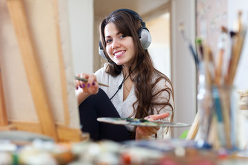 female artist  in headphones paints picture on canvas