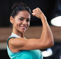 Woman showing her biceps in gym