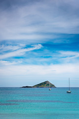 landscape of a small island and sailboats under a beautiful cloudscape at Greece