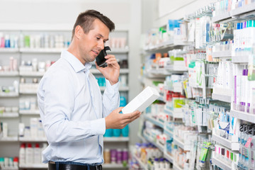Customer Using Mobile Phone While Holding Product In Pharmacy