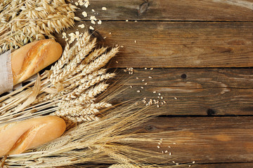 Bread and three types of cereals - wheat, rye and oats on a wood