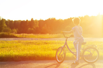 little boy riding bike in summer park at sunset