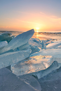 Frozen blocks of ice on the water in winter with a blue sky in the background at sunrise with a golden glow