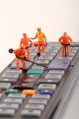 tecnici in miniatura riparano un telecomando