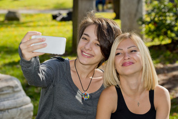 Two beautiful young women taking self photos with phone outside.
