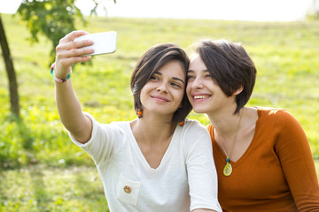 Two Beautiful Young Woman Taking Their Photo In Park