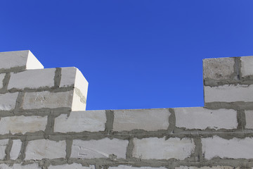 concrete blocks. wall of a house under construction from concrete blocks on a background of blue sky
