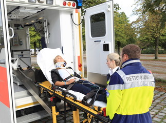 Rettungssanitäter schieben Patientin auf Trage in Rettungswagen