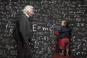 Nonno scienziato e nipotino con lavagna scritta sullo sfondo