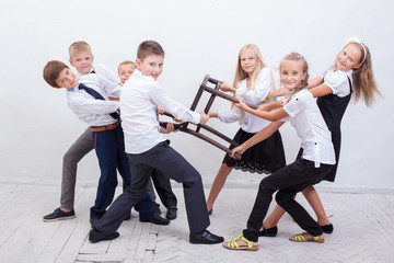 Kids playing tug of chair - girls versus boys,