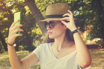 Young woman taking a selfie with cellphone outdoors.