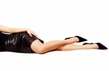 Beautiful legs woman with black leather skirt laying on the bed. isolated on white. black high heels.