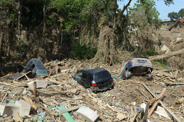 cars lay in  debris after  flood disaster