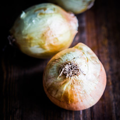 Yellow onions on wooden background