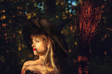 beautiful woman witch with hat and broom in hand on sunset