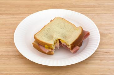 Honey ham sandwich on a paper plate bitten