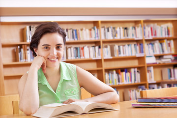 Cute female student reading a book at the library