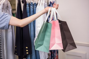 Woman holding shopping bags out