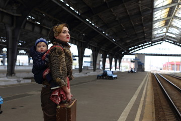 Traveling people, mother and child at the railway station