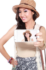 Happy asian woman taking a selfie using her smartphone, isolated on white background