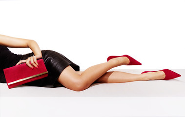 Beautiful legs woman with black leather skirt laying on the table. isolated on white. Red high heels and purse.