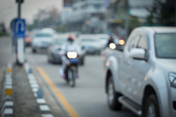 car and motorcycle driving on road with traffic jam in the city, abstract blurred