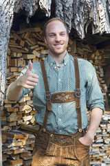 young man in bavarian lederhosen with thumbs up