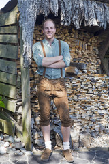 young man in bavarian lederhosen in front of firewood