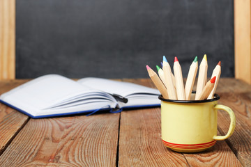 Pencils in a mug, open notebook and chalkboard