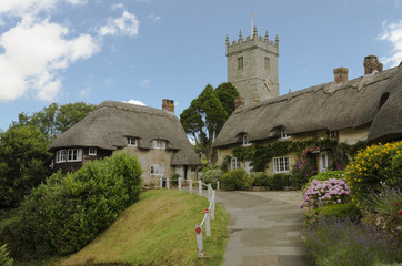 The pretty thatched cottages of Church Hill, with All Saints church in the background.l