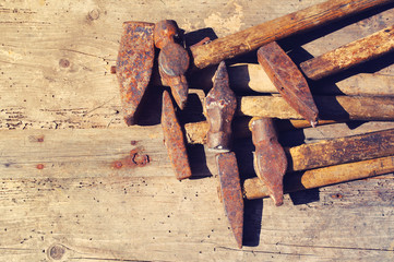 Old rusty hammers on a textural wooden surface. Collection of old hammers. Old tools