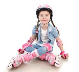 Cute smiling little girl in pink roller skates