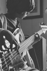 Boy feeling the music as he practices his bass guitar