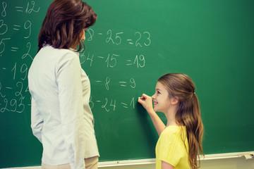 little smiling schoolgirl writing on chalk board